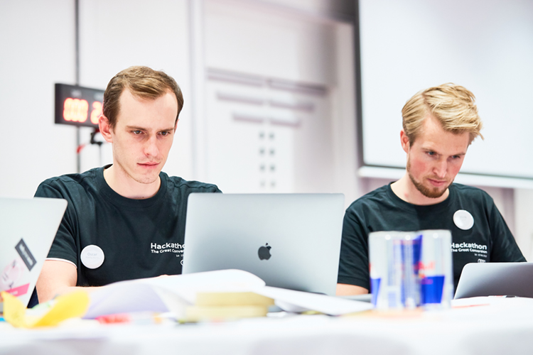 Two team members attending the Hackathon, working on their laptops.
