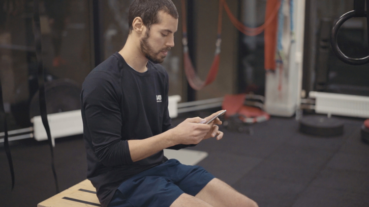 Personal trainer sitting in the gym, using the new PT app.