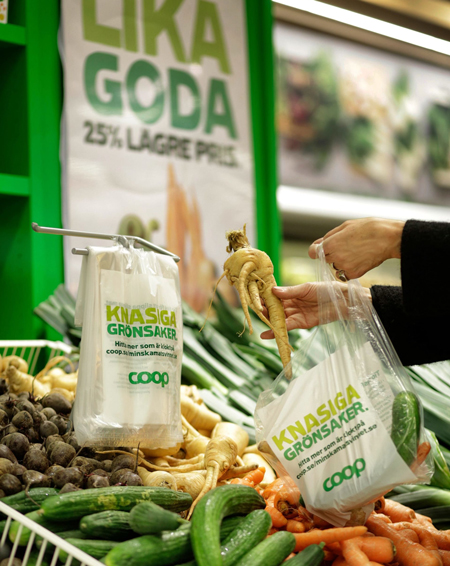 A person picking out vegetables at a Swedish Coop store.