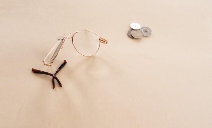 Illustrasjonsbilde av en ødelagt brilleinnfatning og noen mynter