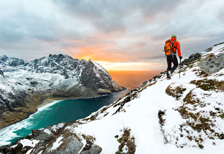 A person hiking on a snowy mountainside, with a fjord and the sunset in the background.