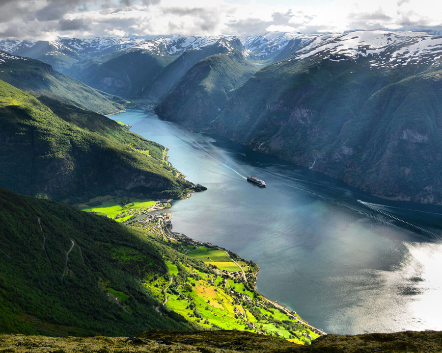 Spectacular landscape shot, showing a cruise ship going down a Norwegian fjord.