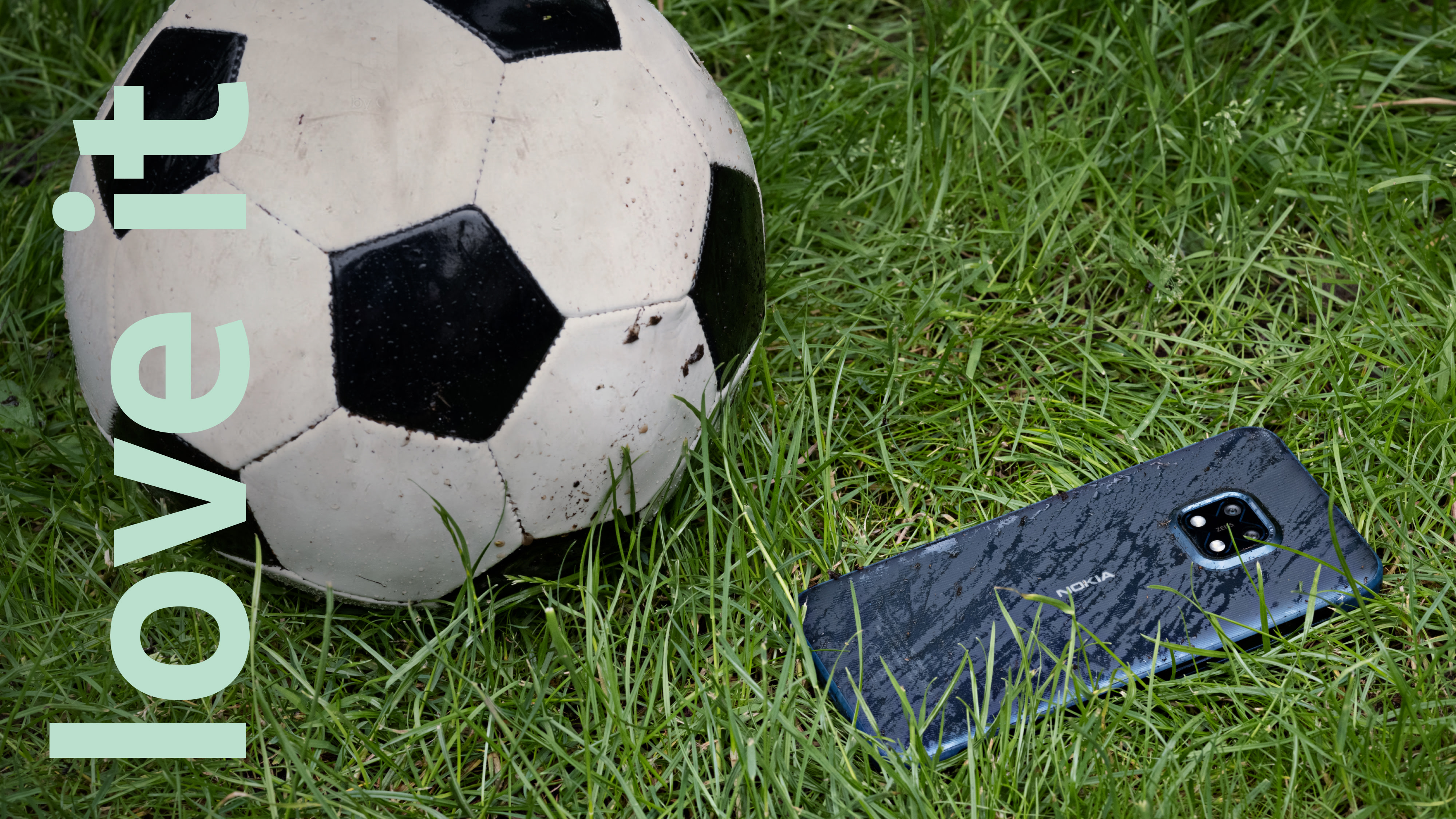 A football and a robust Nokia XR20 smartphone on the grass.