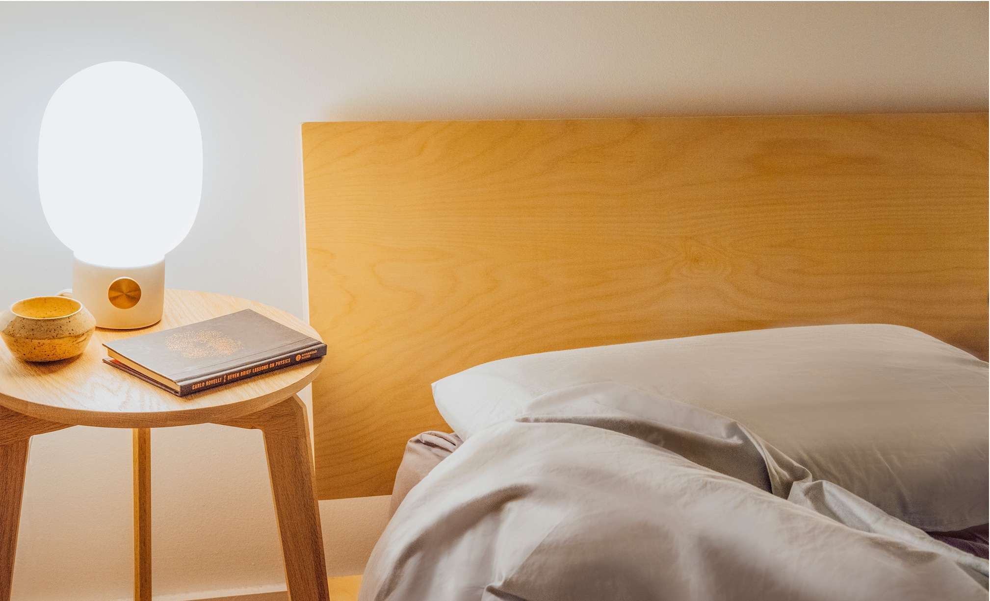 A Floyd bed in birch beside a small nightstand with a glowing light.