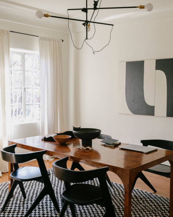 A burled dining table brings color to the otherwise black and white space.