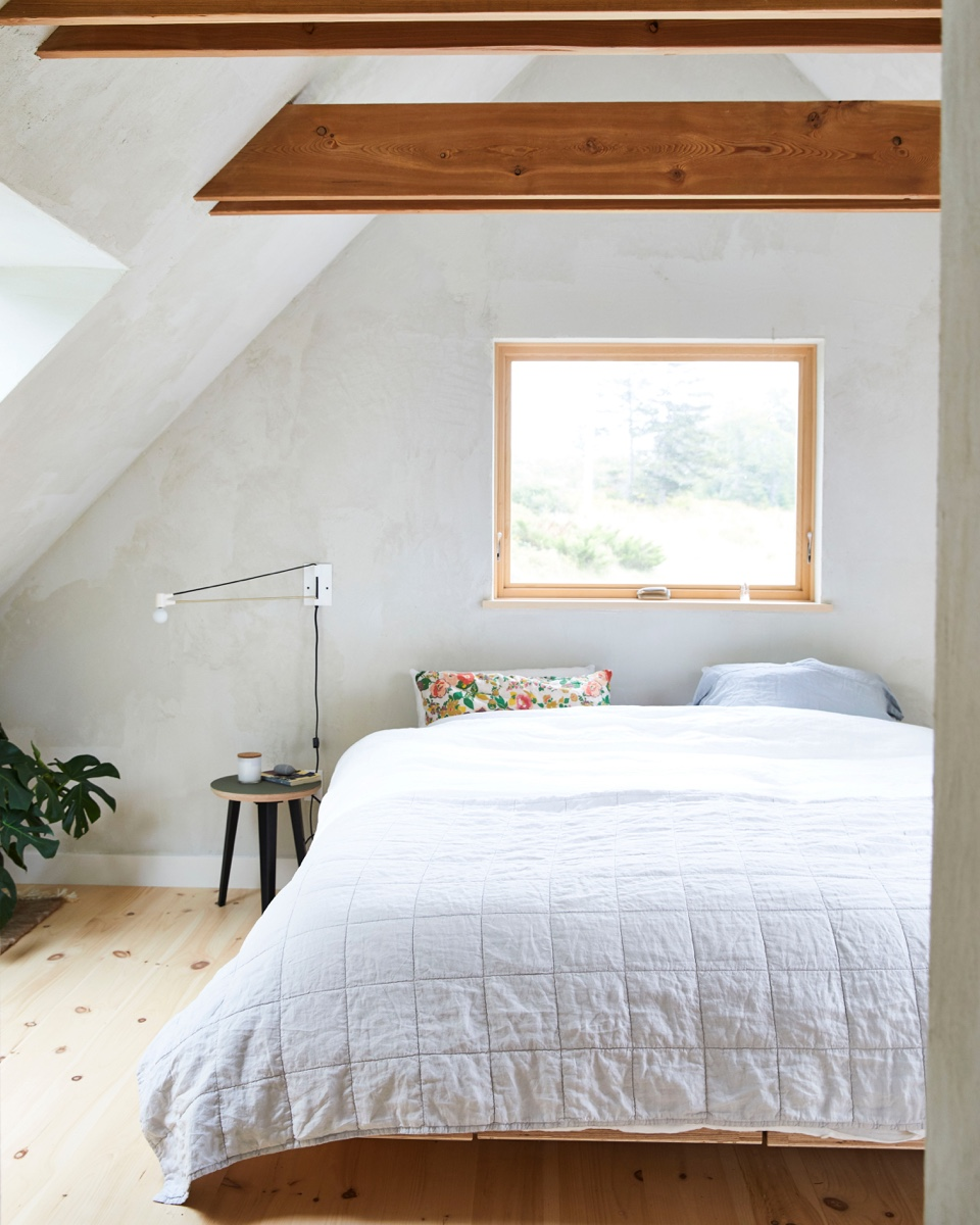 The airy master bedroom takes up the peaked roofline above the great room.