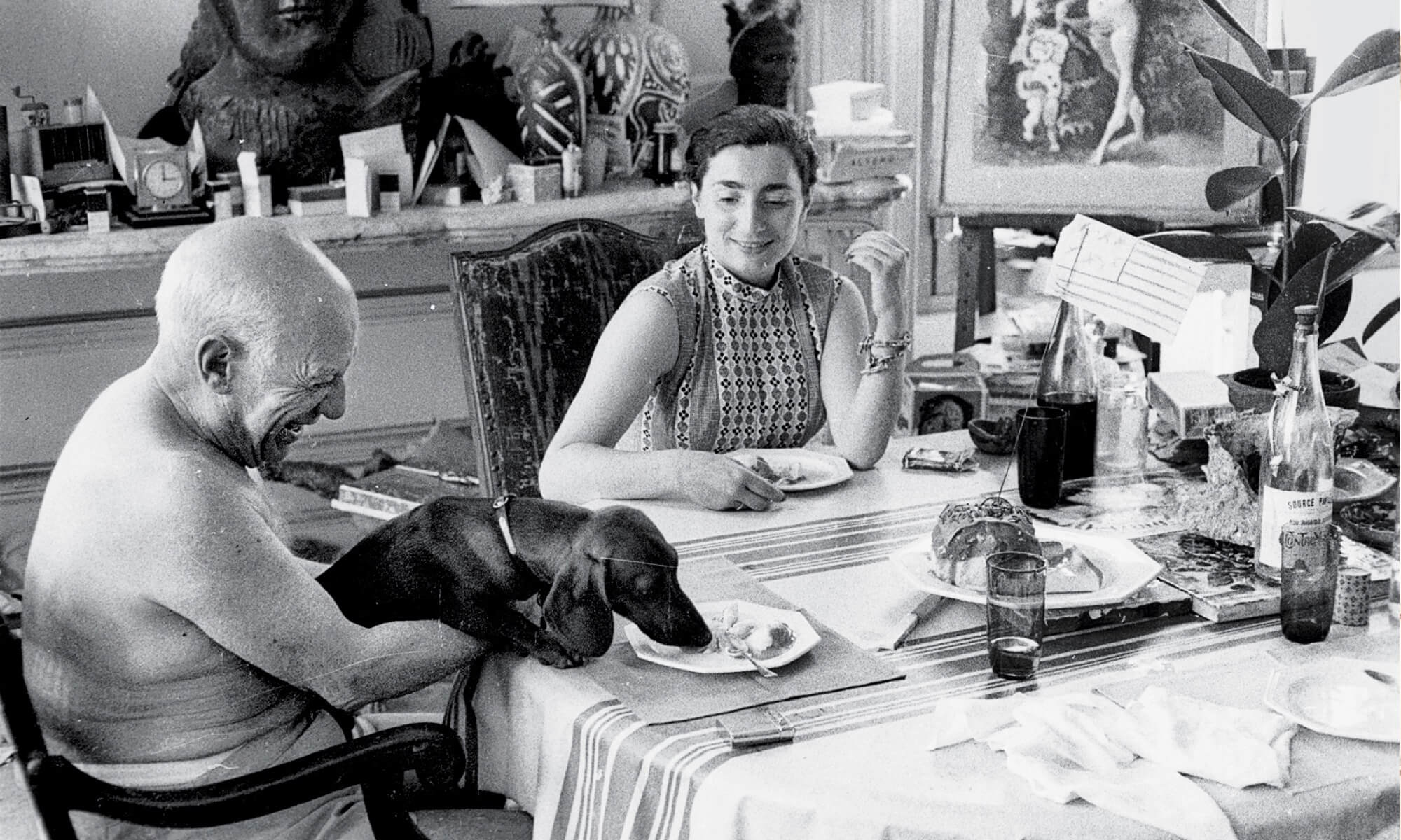 Picasso, wife Jacqueline and his dog at dining room table with buffet table