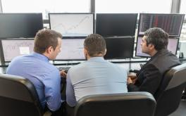 Three men sitting in front of 8 monitors looking at graphs
