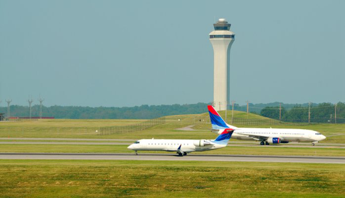 Two airplanes taxiing next to a control tower