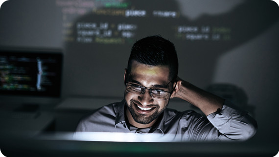 Smiling software developer looking on script on computer screen.