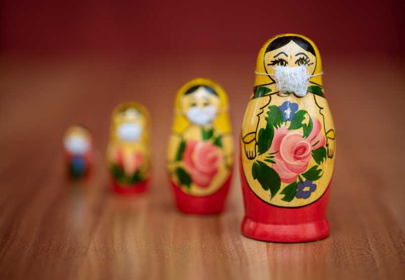 Four Russian Nesting Dolls wearing little surgical masks on a table. The largest and closest one is in focus, the smaller, farther ones are not.