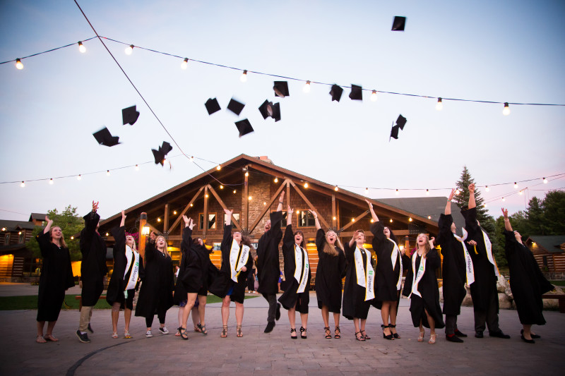 Unbound students throwing graduation caps into the air