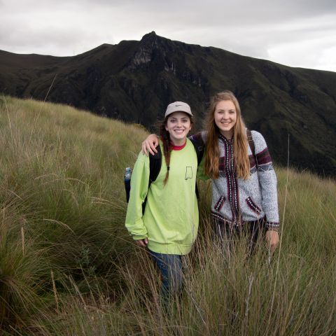 Two girls standing in front of mountain in Ecuador