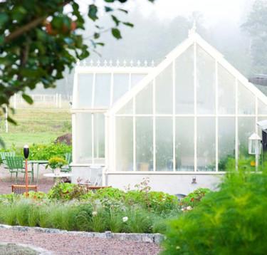 Växthuset Victorian Lodge i vitt gifter sig med naturen runtomkring och skapar en grön dröm. Foto: Vansta Trädgård