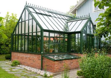 Växthuset är placerat riktigt nära huset men med en liten smitväg mellan byggnaderna. Utanför finns en härlig, odlingsvänlig kallbänk. Foto: Vansta trädgård
