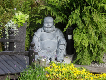 En glad och god Buddha mediterar i Lena Karlssons trädgård.
