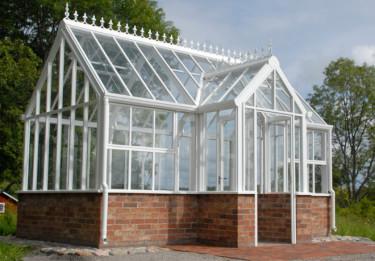 Den teglade grundmuren håller värmen i växthuset. Foto: Vansta Trädgård