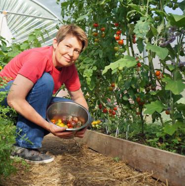 Monika i sitt tunnelväxthus, där tomaterna frodas. Foto: Lena Andersson
