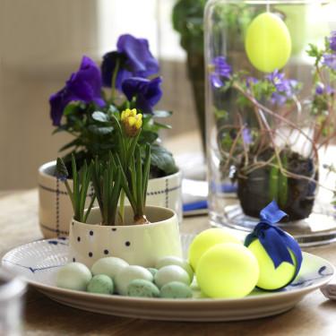 Neongula ägg tillsammans med blåa växter och andra detaljer blir fint till påsken. Foto: Sofie Helsted och Mille Fly