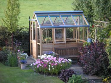 Det lilla växthuset 'The Six' med träpanel.