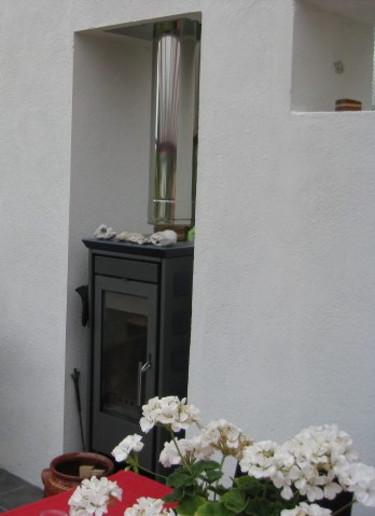 För att förlänga säsongen för uteliv finns en kamin i en öppning i muren.