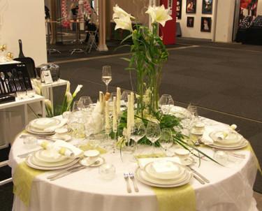 Duka hade dukat upp ett festbord på mässan med vit duk och limegröna avlånga bordstabletter. Blomsterarrangemanget med rosor, orkidéer och liljor är fiffigt, gästerna ser lätt varandra.