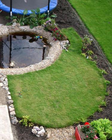 Den lilla gräsmattan är avskuret rund, för att komplettera den runda studsmattan och den runda dammen. De 5 kvadratmetrarna rullgräs räckte precis.