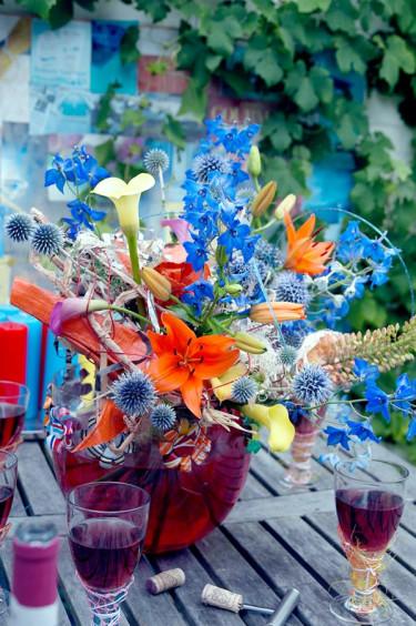 Duka upp till vårbuffé med en vild bukett av lilja, _Lilium_, riddarsporre, _Delphinium_, stäpplilja, _Eremurus_, bolltistel, _Echinops_ och kalla, _Zantedeschia_.