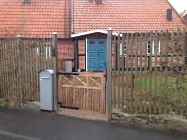 Ett luftigt plank med en grind som är lägre och visar att visst vill huset ha besökare.