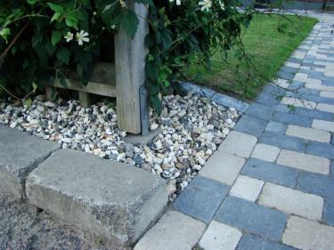Sten och singel med markduk under håller ogräset borta.