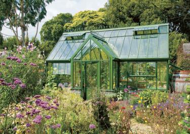I den täta grönskan smälter ett grönt växthus in fint.  Foto: Vansta Trädgård
