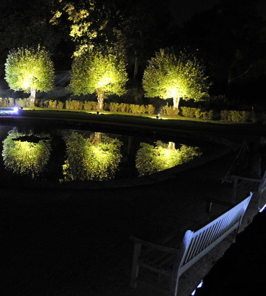 Belysta träd som speglar sig i dammen i Gunnebo Foto: Sylvia Svensson