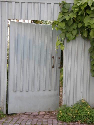 Piprankan som klättrar vid porten mjukar upp känslan och väcker nyfikenhet. Vad döljer sig där bakom?