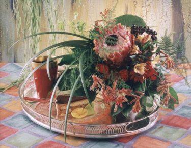 Protea, Kängurutass, Alstromeria, Daggkåpa, Fläderbär, Texasgräs, Plumosus, Salal, Araliablad och röda rosor utgör en maskulin men ändå vacker bukett. I bakgrunden syns en Hoya. Foto: Bo Appeltoft.