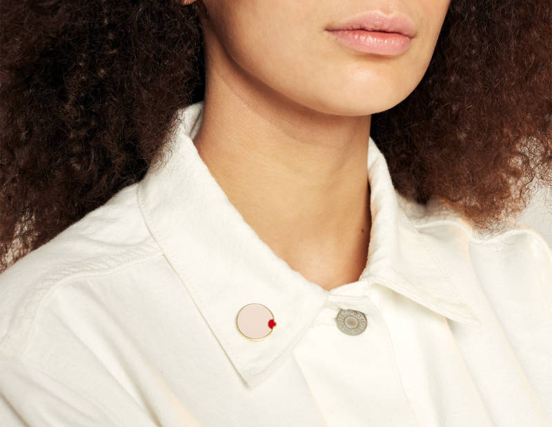 """Your Kaya """"breast"""" pin on the collar of the jacket"""