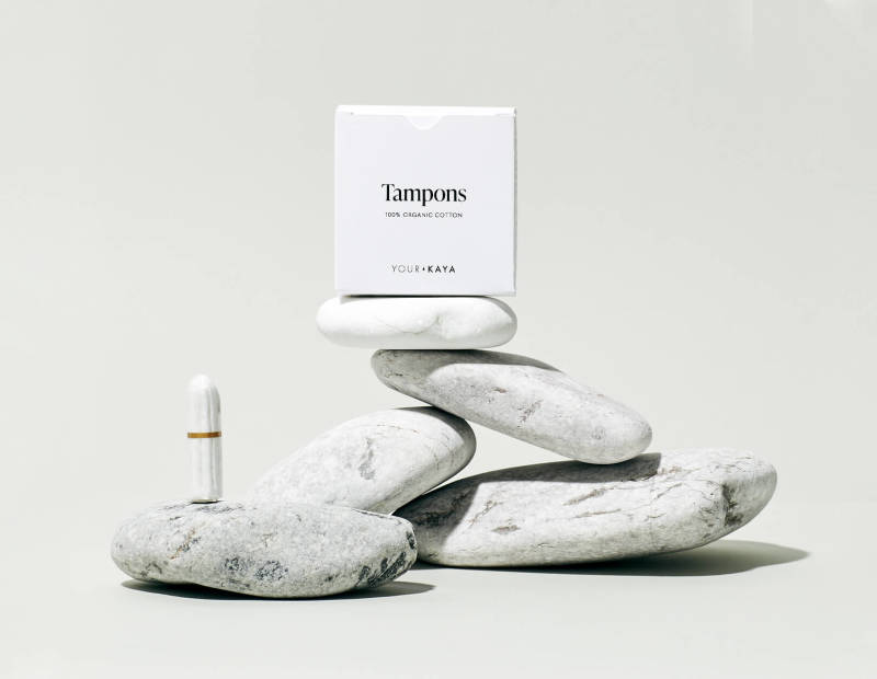 Your KAYA organic cotton tampons in a composition with stones