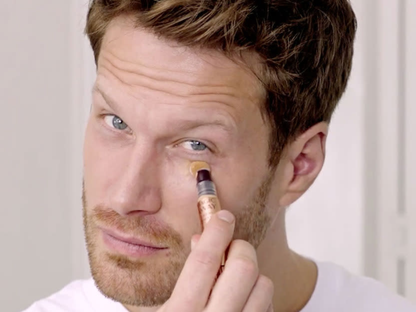 Charlotte Tilbury male model applying Magic Away concealer