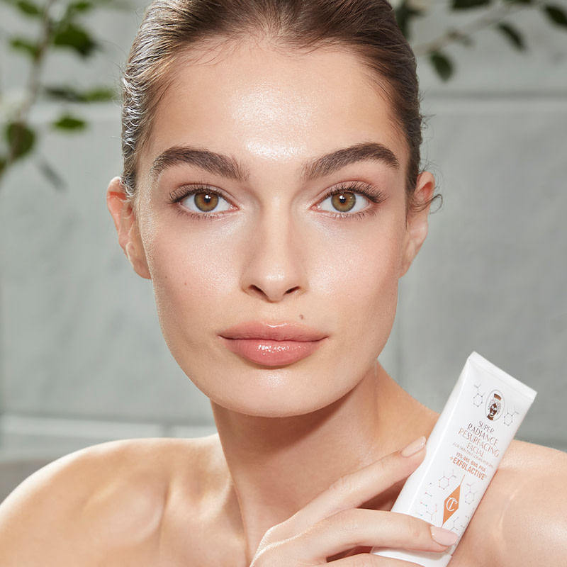 Model Adela holds Super Radiance Resurfacing Facial face exfoliator
