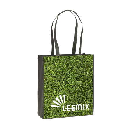 A shopping bag with a photo of green grass printed on the side, available at Helloprint for a cheap price