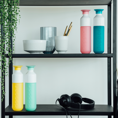 Printed bottles of doppers, on a design shelf with a plant, customizable doppers on Helloprint