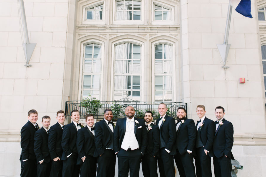 Renting vs buying your wedding tuxedo weddingwire groom and groomsmen black tuxedos outdoor junglespirit Choice Image