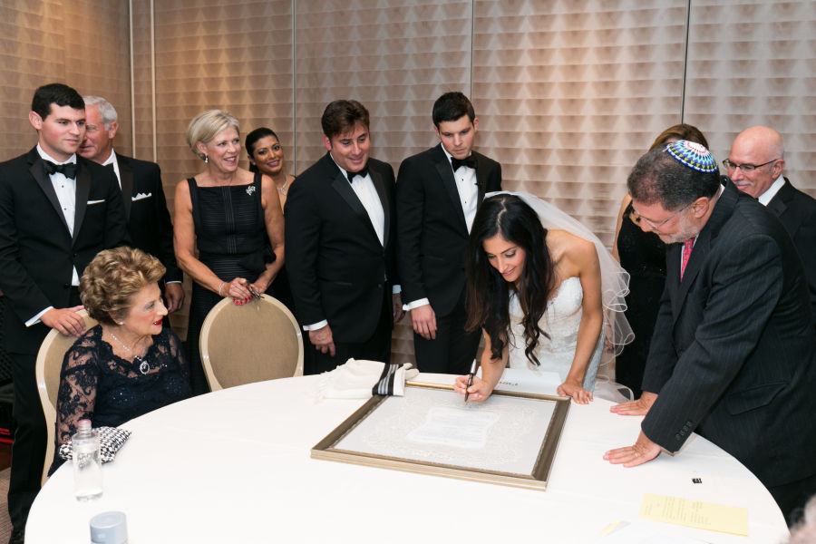 Jewish Couple Signing Wedding Ketubah