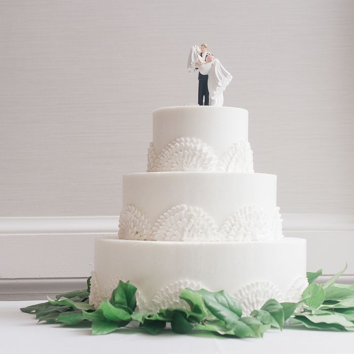 White Wedding Cake With Bride Groom Topper And Greenery At Base