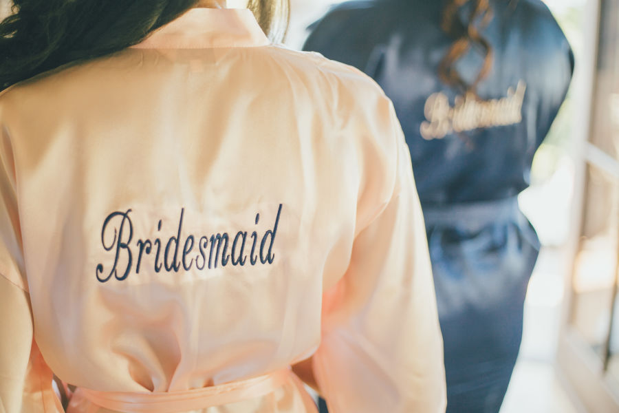 bridesmaid wearing pink labeled robe