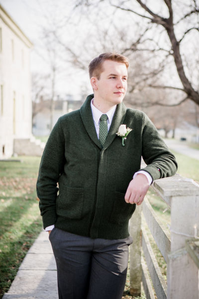 Groom In Thick Green Cardigan Over White Button Down Checkered Necktie Floral Boutonniere Gray Pants