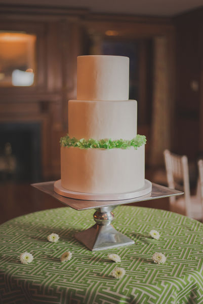 Three Tiered White Fondant Wedding Cake With Green Frosting Around The Top Of Third