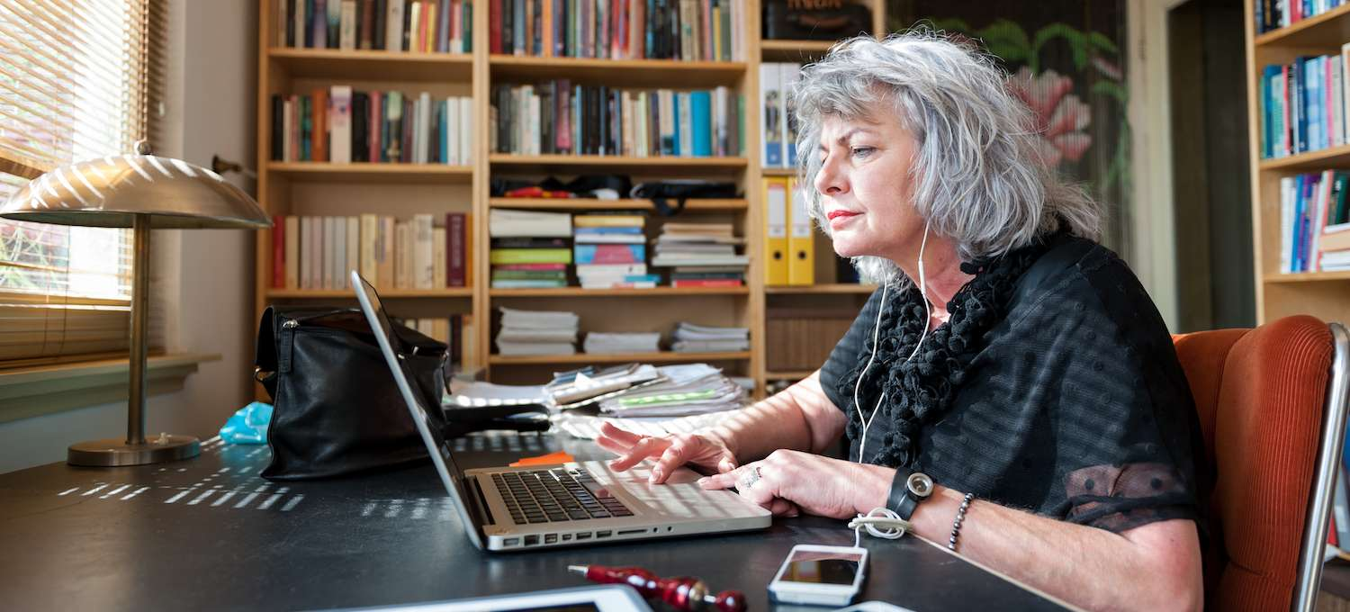 A professer sits in her office writing on her laptop with many bookshelves behind her
