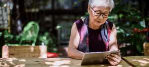 An older woman sits outside at a wooden table reading a book on her tablet device.