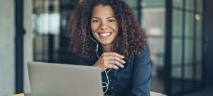A woman working as a ethical hacker or penetration tester sits in front of her work laptop and wears headphones.