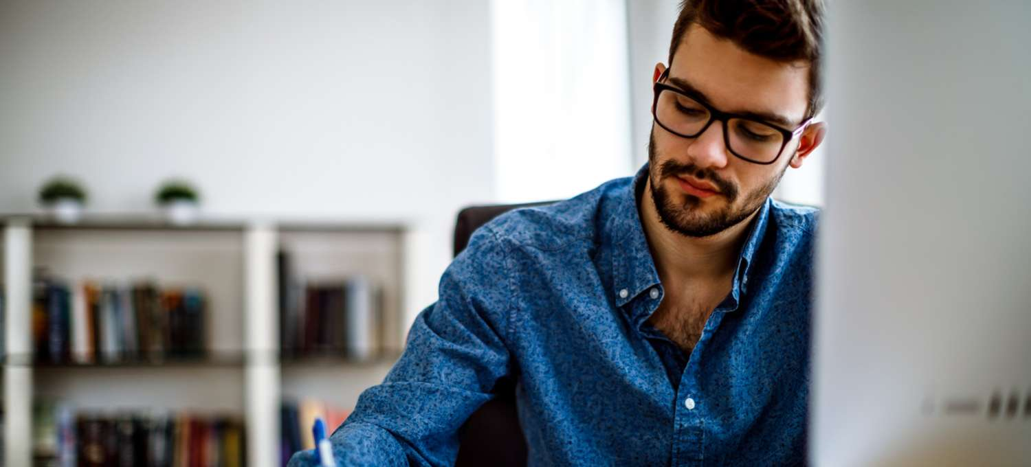 Man with glasses and a blue shirt working on his master's degree in front of a computer